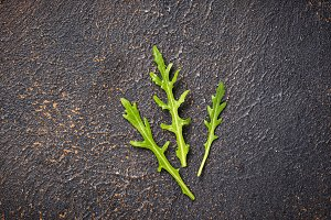Fresh arugula leaves on rusty table