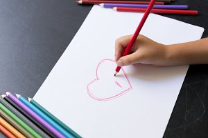 Kid's hand with pencil draws heart