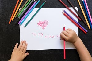 Kid's hands with pencil draws heart