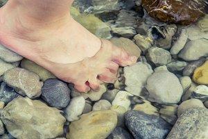 child barefoot river gravel
