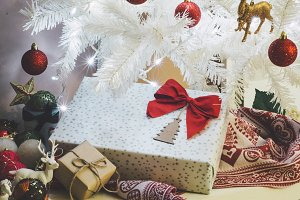 Gift with red bow next to the white