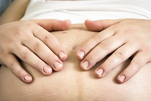 Hands of a pregnant woman caressing