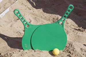 Two rackets and a ball on the sandy