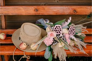 wedding bouquet lies near hat on