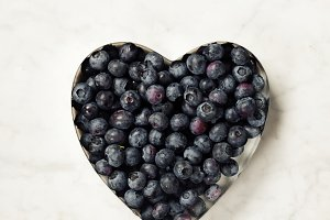 Heart shaped blueberries on marble b