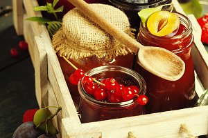 Fruit and berry jam on a wooden back
