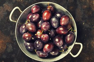Plums in a bowl on a rural backgroun