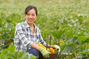 Happy woman harvesting vegetables