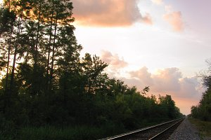 Railroad train tracks at sunset