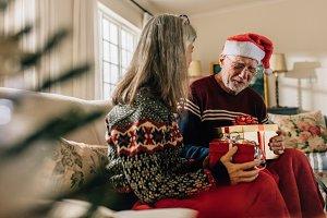 Senior couple exchanging christmas