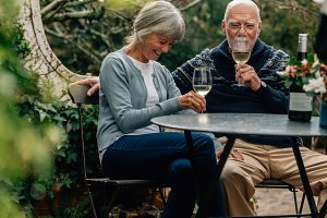 Old couple enjoying a glass of wine