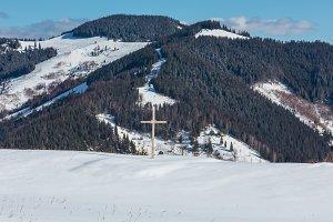 Cross on winter mountain hill top