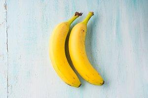 Two bananas on green pastel