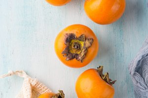 Ripe persimmons on turquoise