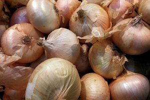 piled sweet onions at market