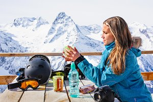 Woman snowboarder drinking tea.