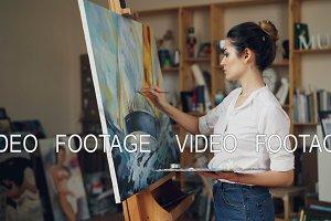Glad female artist is painting