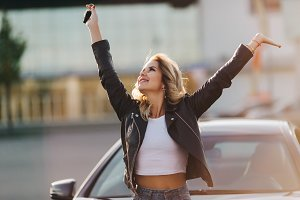 Photo of woman with raised hands and