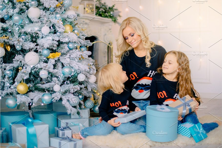 young mother gives gifts to her ~ People Images ~ Creative Market
