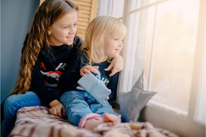 two little girls look out window on