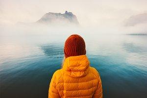 Woman alone looking at foggy sea
