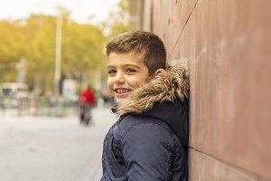 Little boy leaning on a wall. Urban