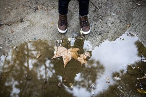 The feet of a child next to a puddle