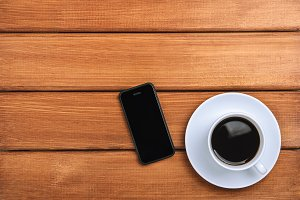 A cup of hot coffee and mobile phone