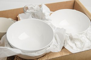 Clean white dishes in cardboard box