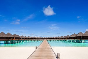 Water bungalows and wooden jetty on