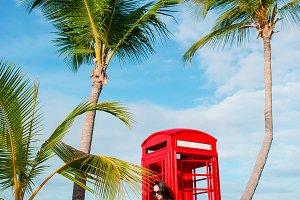 Beautiftul woman near red phone boot
