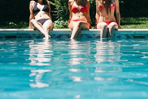 Women sitting on the edge of a pool