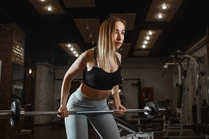 Young woman lifting barbell with