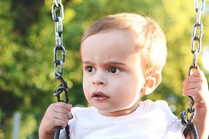 Cute baby boy having fun on a swing