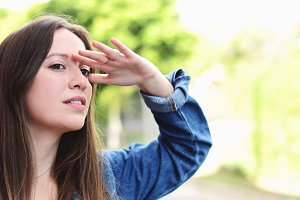 Young woman looking far with hand at