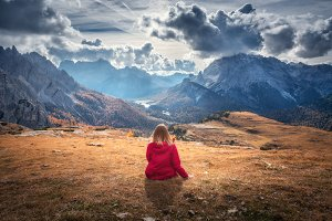 Woman is sitting on the hill
