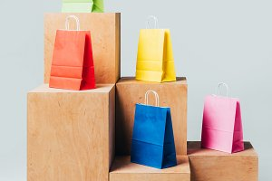 colored shopping bags on wooden stan