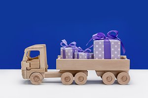Wooden toy truck with gifts in boxes