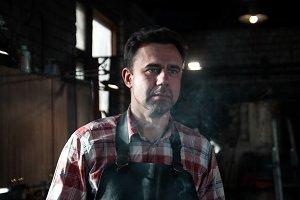 Blacksmith in leather apron smokes
