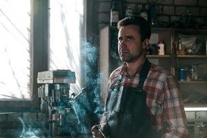 Blacksmith in leather apron smokes a