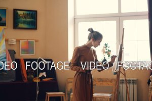 Cute young woman painter is working