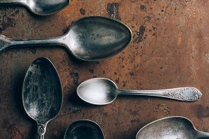 top view of silver spoons on grungy