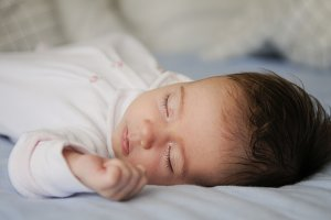 Newborn baby girl sleeping on blue s