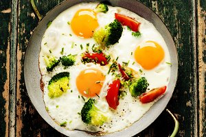 Pan of fried eggs, broccoli and cher
