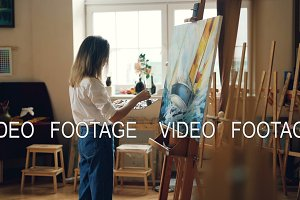 Slender blond girl is painting