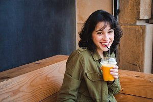 Happy young woman drinking a fruit s