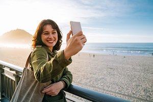 Happy tourist woman taking selfie wi