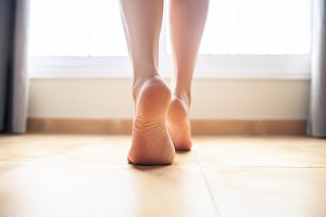 Woman bare feet walking on floor
