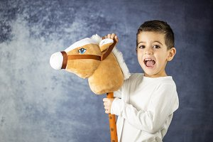 Little kid playing with a toy horse