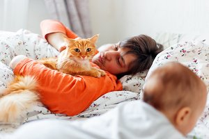 Man with baby and ginger cat in bed.